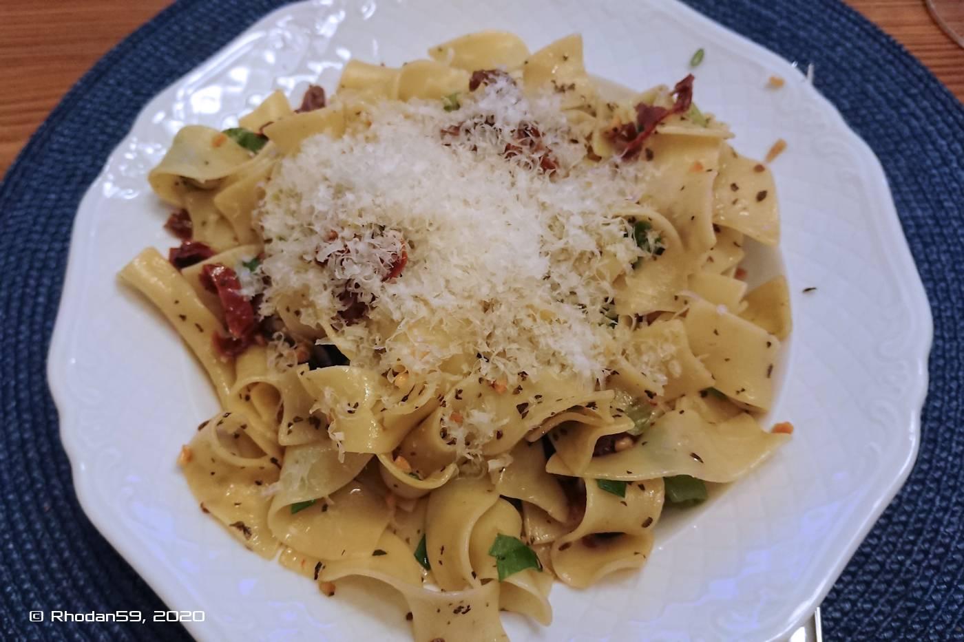 Bandnudeln mit Champignon und getrockneten Tomaten im Teller